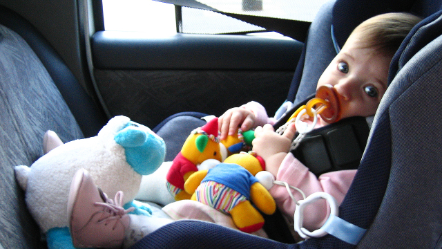 Toddler sitting in car seat.